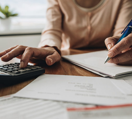 A woman using a calculator - Excess Protect Insurance with Rockland Insurance Brokers