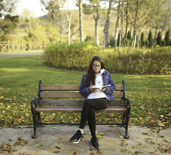 Girl sitting on the bench at the park and reading a book. - Rockland Insurance Brokers