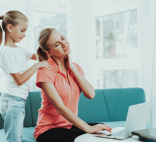 Daughter giving mother a back massage at home - Rockland Insurance Brokers